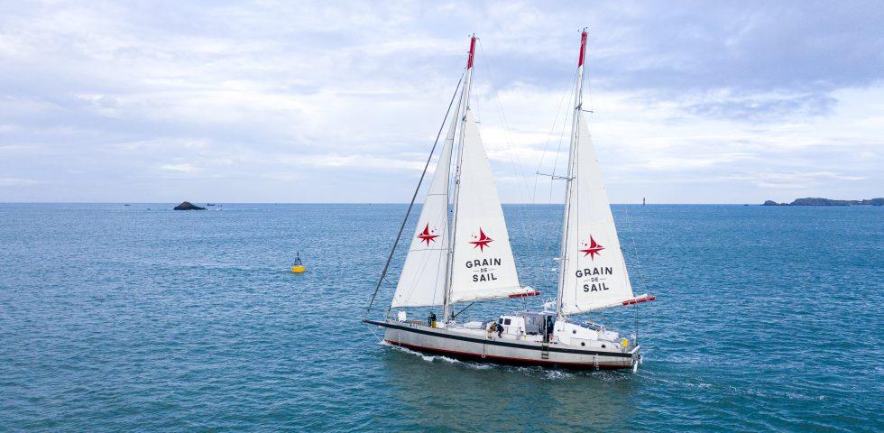 """The """"Gran de Sail"""" boat sailing along a coastline"""
